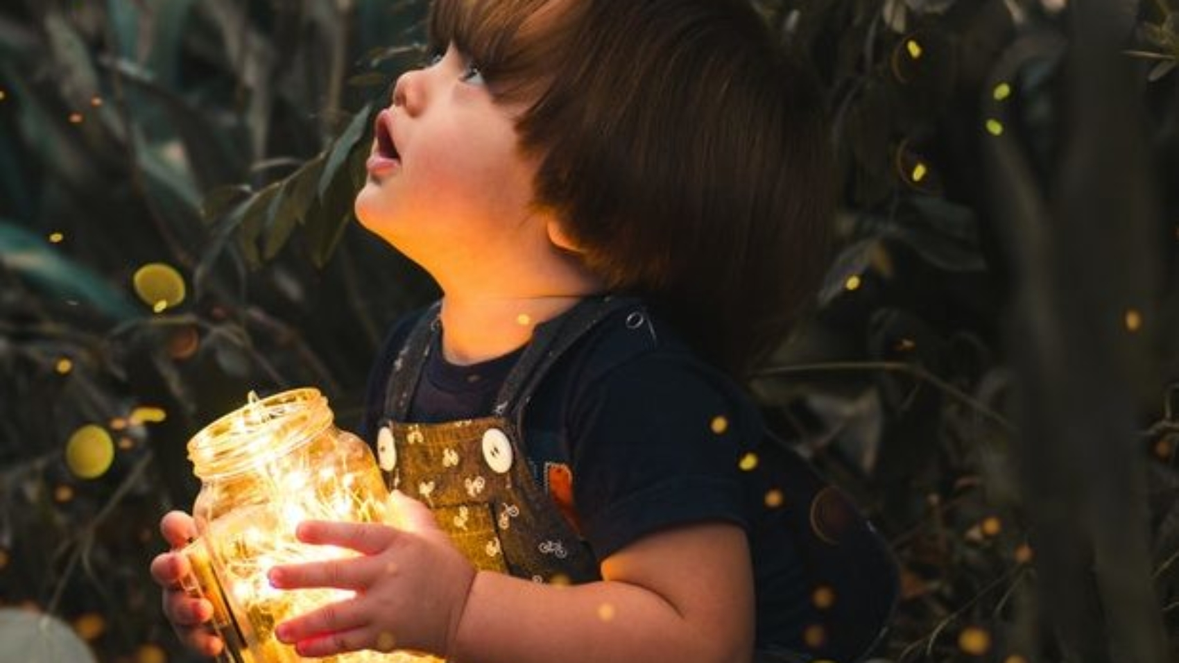 child-holding-clear-glass-jar-with-yellow-light-2026960