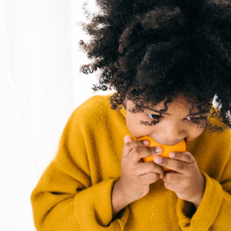 hungry-ethnic-child-eating-ripe-orange-in-studio-4546118